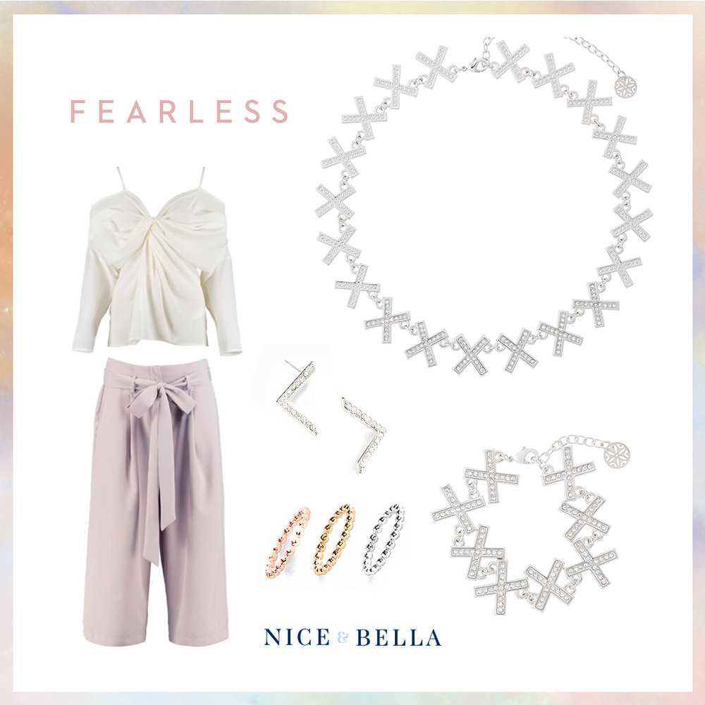 Demonstrate fearlessness in these lavender trousers and off-white, strappy blouse. It's paired with crystal encrusted, rhodium earrings, bracelet and necklace. A pop of color is shown with a trio of rose gold, gold and rhodium rings.  SKU'S:   118041L, 118049L, 118123, 118497