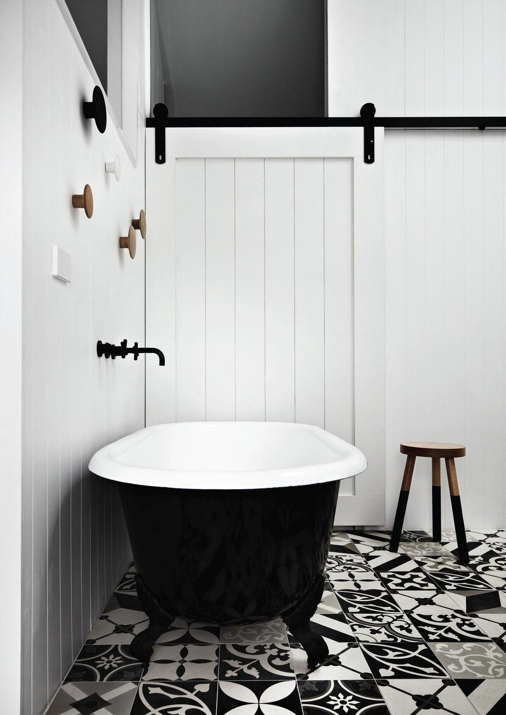 a-chic-classic-black-and-white-bathroom-with-patterned-flooring-and-black-bathtub-also-white-wooden-sliding-door.jpg