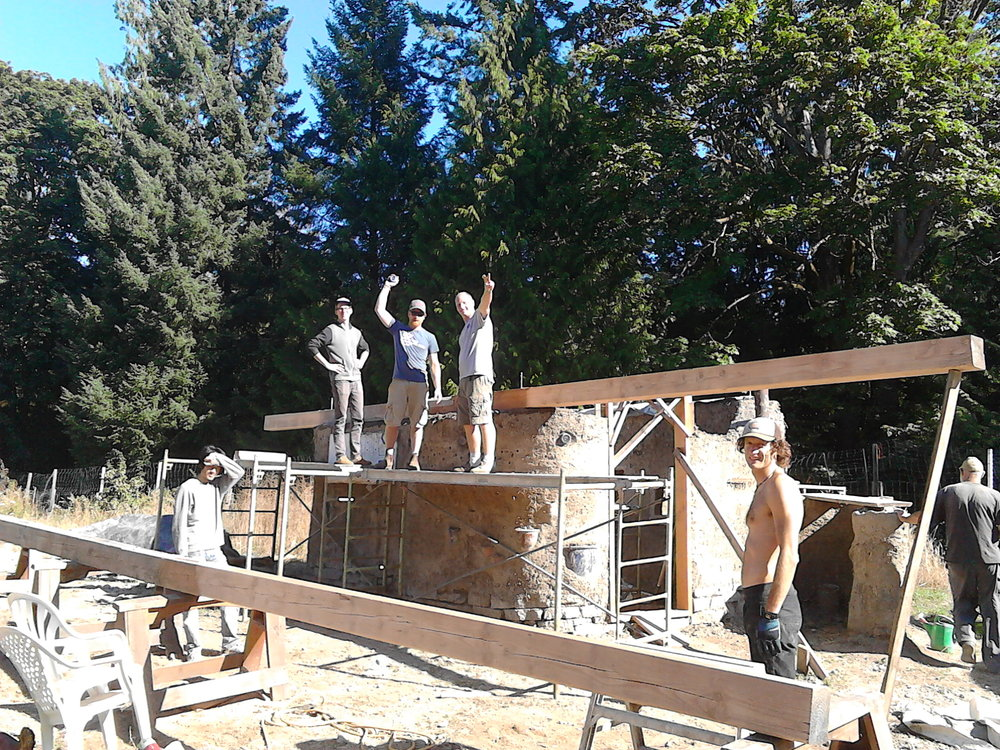 """Lifting our roof beams in place with students on the """"garden cob"""", which will later be 3 season accommodation for guests or staff."""