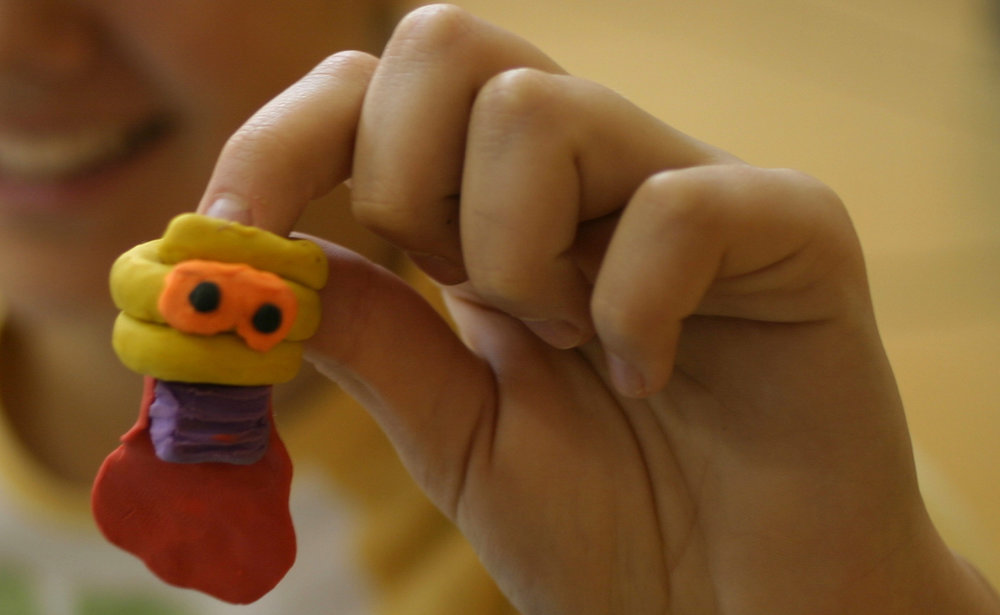 """A Montessori middle school student shows off a unique clay character she created for an animated movie about technology. ReadyANIMATOR provides a """"blank slate"""" that encourages outside-the-box creativity from students."""