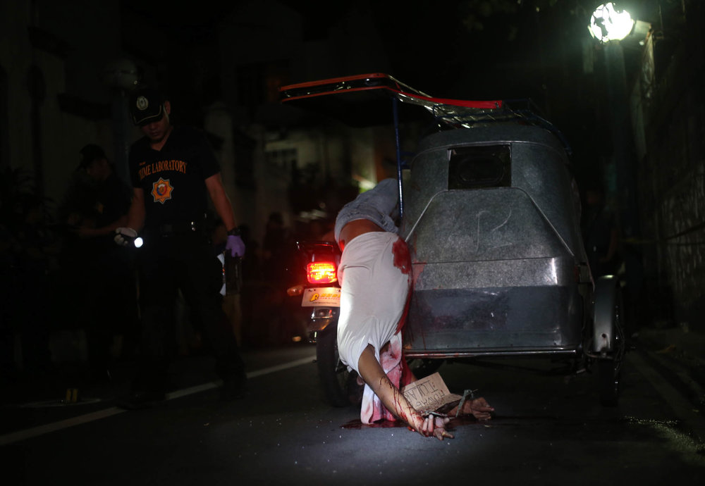Alleged drug pusher Redentor Manalang is found lifeless on his tricycle after being shot and killed by riding-in-tandem suspects in Protacio St, Pasay on July 23, 2016.