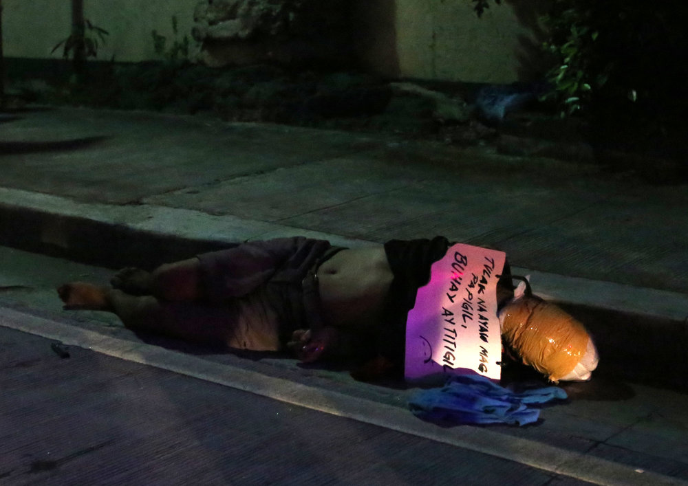 "A victim of summary execution is dumped at Florentino Street, Sampaloc, Manila on October 1, 2016. A cardboard was left with words, ""Tulak na ayaw magpapigil, buhay ay titigil"" (A pusher who won't stop will have his life ended)"