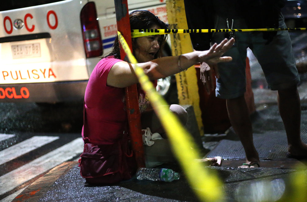 An incosolable Rose Mendoza reaches out to hold her husband Archie Mendoza who was shot and killed by still unidentified persons at Rizal and 10th Avenue, Barangay 91, Caloocan City on October 11, 2016.