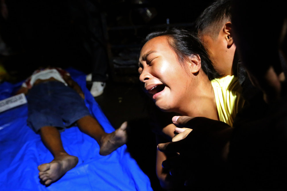 A child grieves over the death of her father Reynaldo Mendoza, an alleged drug pusher who was killed by police during a drug buy-bust operation inside his shanty home along Dagupan Street, Tondo, Manila on November 26,2016.