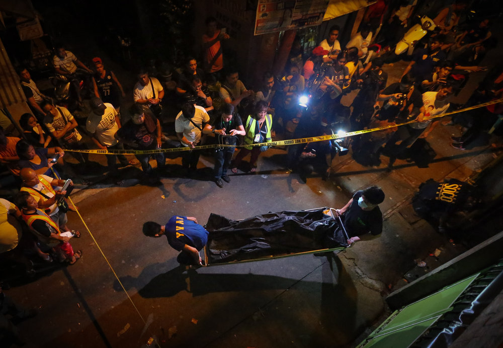 The body of one of three alleged drug dealers killed during a buy bust operation is carried away from the crime scene at Cahilom corner Apitong St., Barangay 872, Pandacan, Manila on July 16, 2016.
