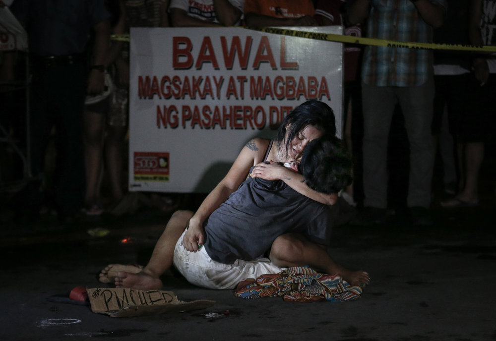 "Jennilyn Olayres holds her partner Michael Siaron, 30, a pedicab  driver, who was shot and killed by unidentified riding in tandem suspects along LRT Pasay Rotonda, Edsa on July 23, 2016. A placard was left beside the victim's body with words, ""Pusher ako, wag tularan."" (I'm a pusher, do not copy me.)"