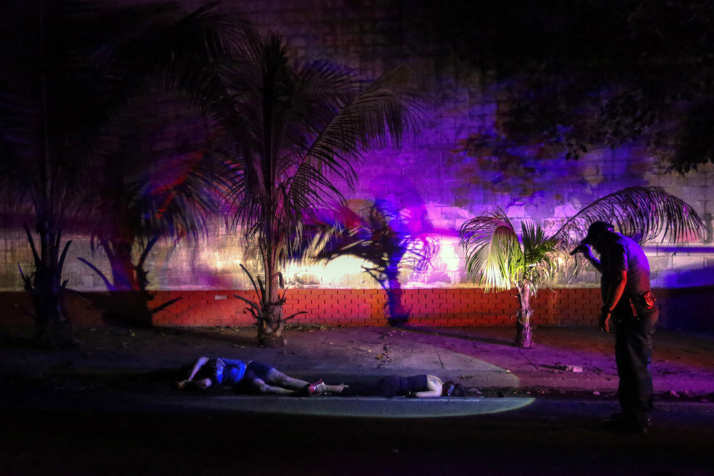 A police flashes light onto the bodies of summary execution victims Janice Peralta and Rachel Santiago outside Paco Park, Manila on July 21, 2016. The victims were found dead with their hands tied and their faces concealed with duct tape.