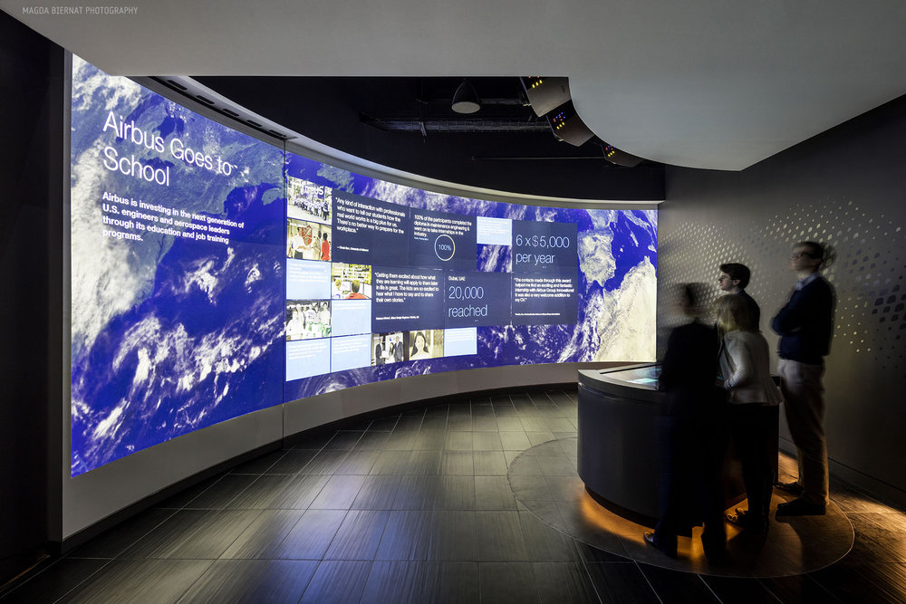 In the Briefing Room, a sweeping 30-foot wall stands in front of a touchscreen table where visitors can intuitively explore featured Airbus Group stories.
