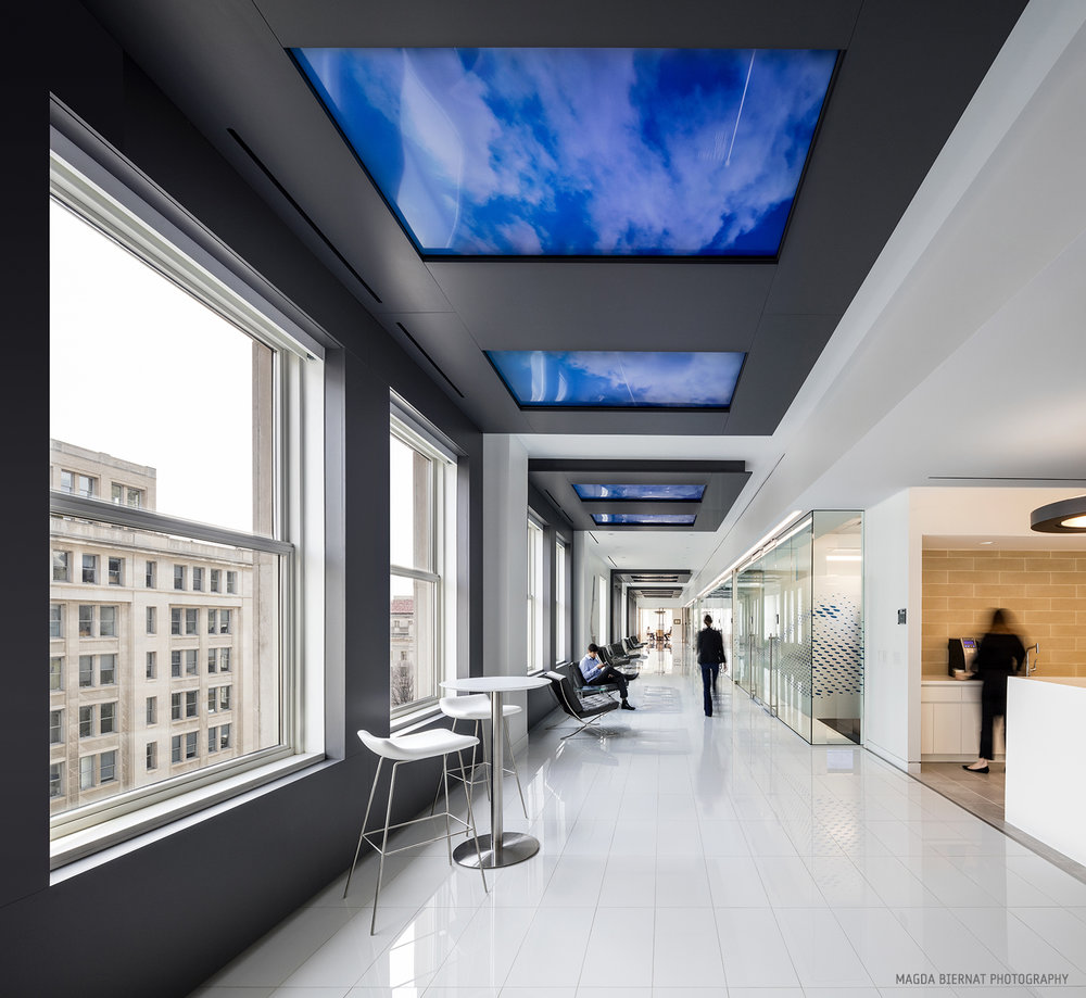 Traveling between the showcase and collaborative workspace, visitors walk the Skywalk Corridor. Ten windows line the ceiling, each with high-resolution motion graphics that evolve from the daytime Contrail view which tracks flight patterns, to Galaxy mode with views of satellites orbiting the night sky.