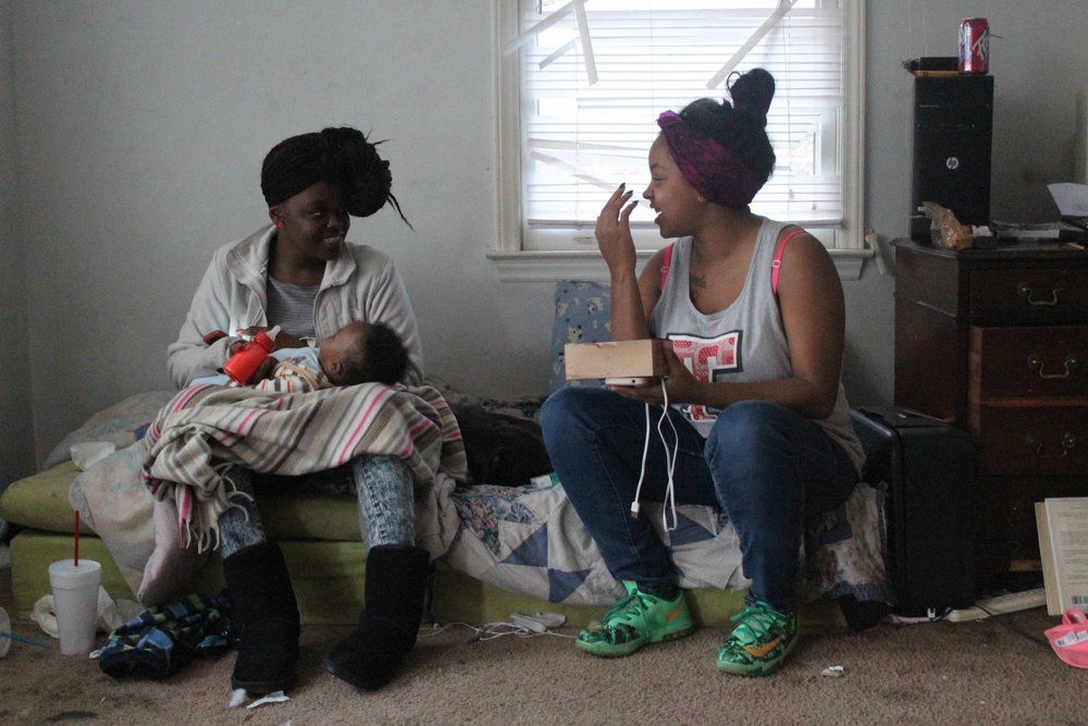 Equashia's daughter, Safiyyah Mumin (left), feeds her son while chatting with a friend. Before the eviction, the Cecil Street house was always full of people. Equashia's guests consisted of members from both the Bloods and the Crips, rival gangs that occupy Durham. While there was often conflict when the boys were out in the world, they usually spent their time at Cecil Street playing video games with one another.