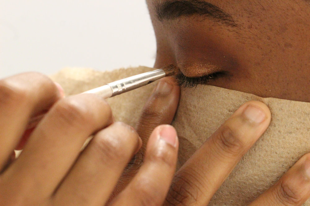 The girls all meet in Coach K's classroom at 6:00 pm to get ready for the game. Here, Kennedi Bulla meticulously paints Lazayrea Smith's eye makeup, using a paper towel to create perfect lines.