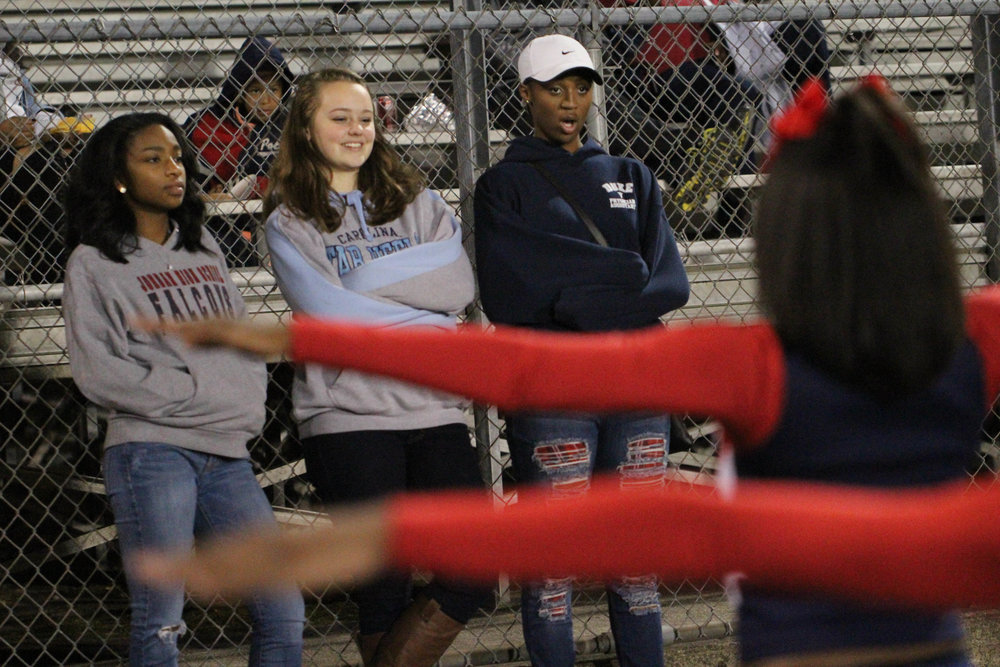 "Tracy Childress, Britney Overbeek and Nyah Hasan (left to right) watch their team perform at the final football game of the season. Coach K removed them from the game because they missed practice for a mandatory choir rehearsal. ""It sucks that we have to sit out the last game, but I'm just glad I got to cheer on Senior Night,"" says Nyah, the only senior on the team. ""It's been hard being older than the rest of the girls, but I think they look up to me. I guess that's kind of cute."""