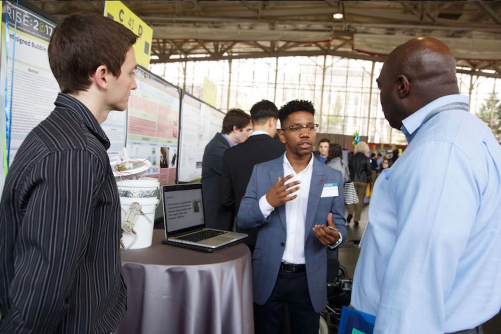 Therapeutic Innovations engineer (L) and business manager (m), explaining research concerning the Airbaby to NASA's Mr. Eric McGill.   Click for article.