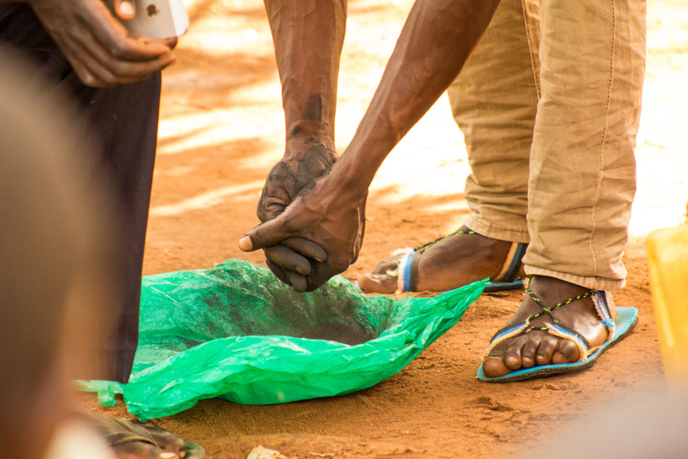 During handwashing triggering, the WASH team uses charcoal as a stand-in for feces to demonstrate how dirt sticks to hands and under fingernails.