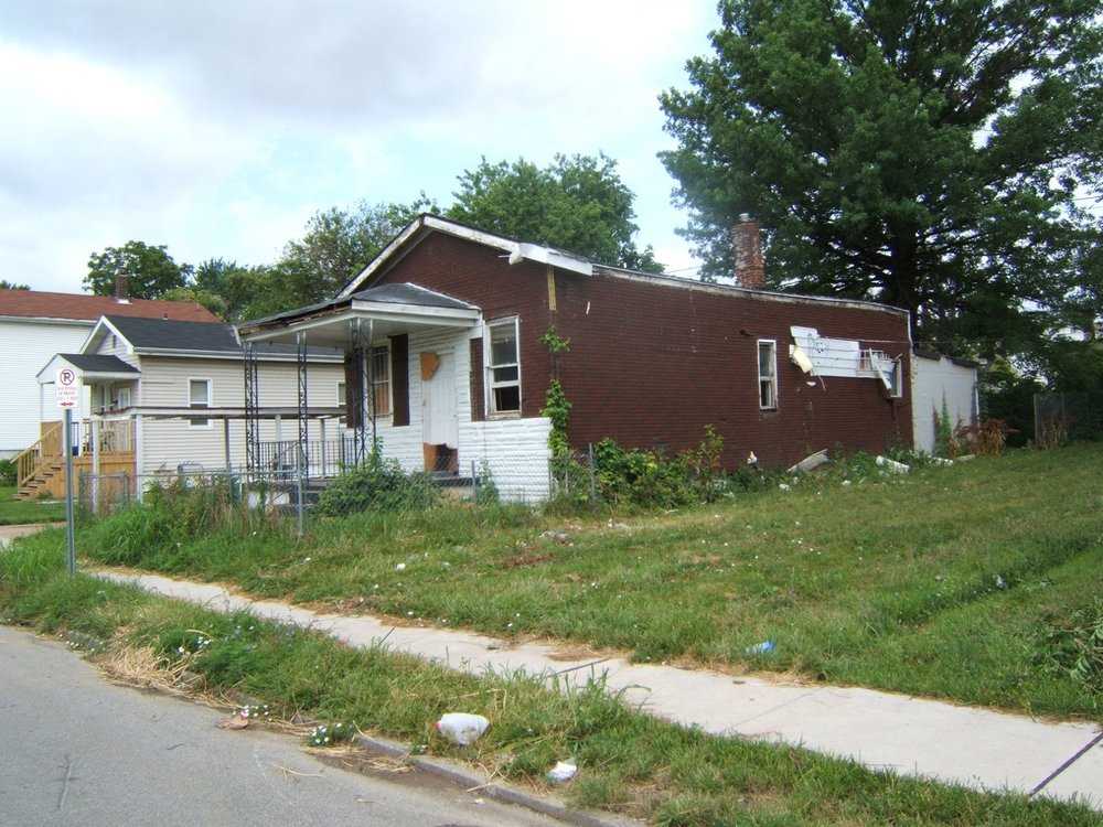 Dilapidated houses (foreground) are systematically demolished by Union West Florissant Housing Solutions. A new Habitat for Humanity house is visible beyond (beige house at left)