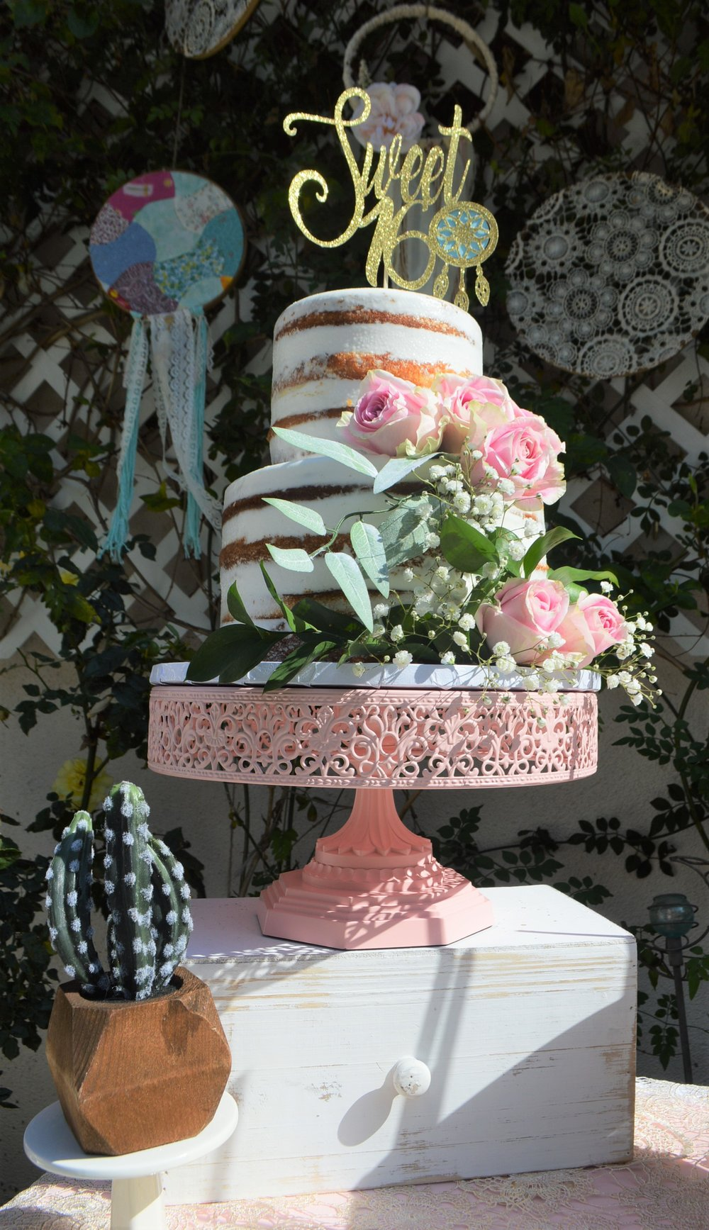 "A naked cake is perfect for any bohemian style party. This gorgeous naked cake sits on top of one of  Amalfi Decor  12"" inch pink cake stands ( which was in the perfect shade of pink).    To get this look  :  -Simply purchase a naked cake from your local bakery or preferred baker.  -Get a pack of fresh eucalyptus and roses (which I got from Trader Joes)  Baby's breathe floral - can be purchased from florist shop  ""Sweet 16"" dream catcher cake topper :  Cake Topper   Cake stand:  Amalfi Decor"