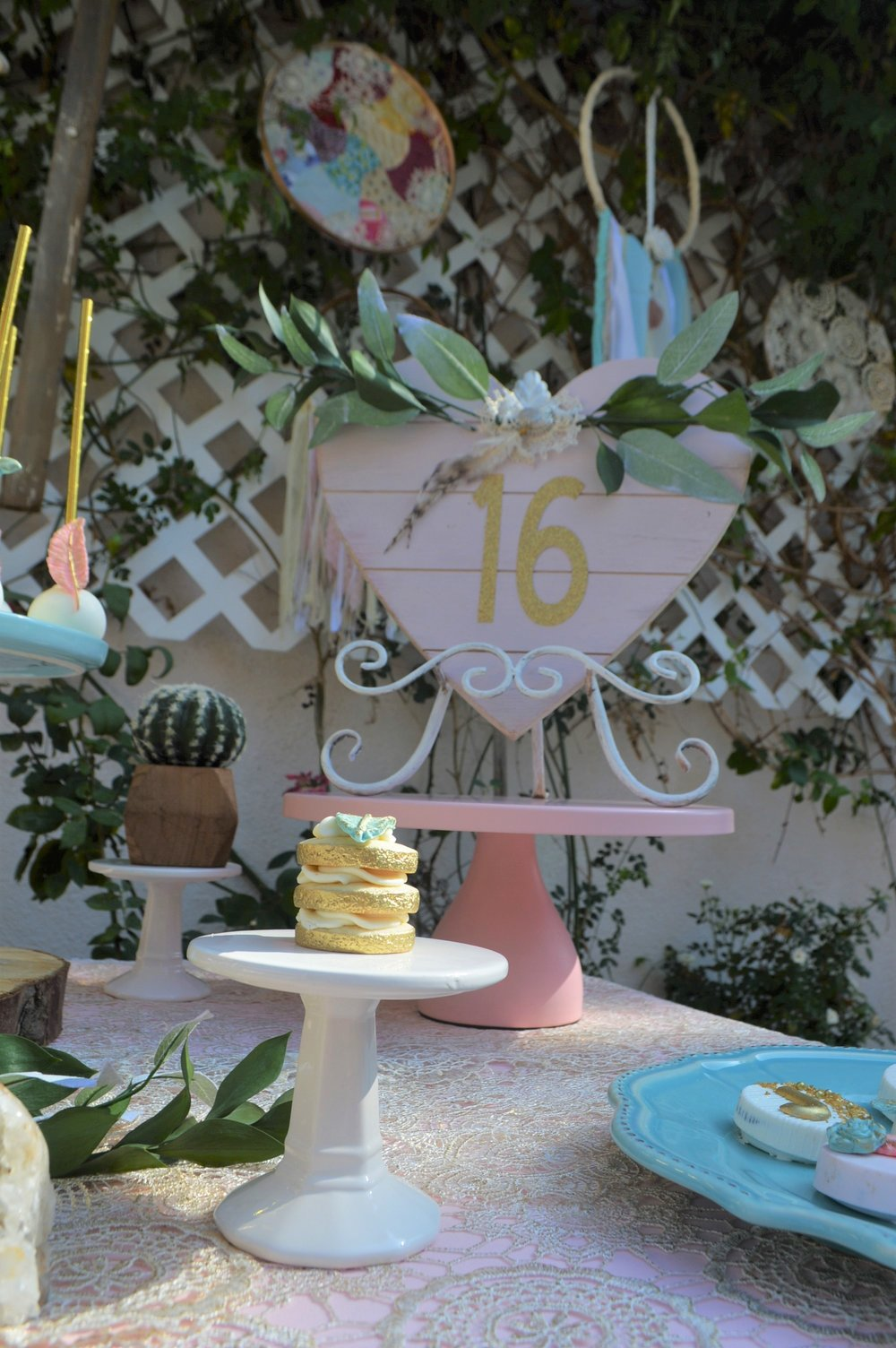"I created this fun ""16"" heart shaped sign by painting a wooden heart shaped wooden frame that I had found from Targets dollar spot. I added the number ""16"" in the middle and used some extra eucalyptus that was left over from the cake to garnish the top of the frame.  Pink stand:  Amalfi Decor"