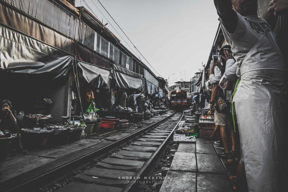The train arriving on Maeklong Railway Market. Thailand, photography by Andrew Mckenna.