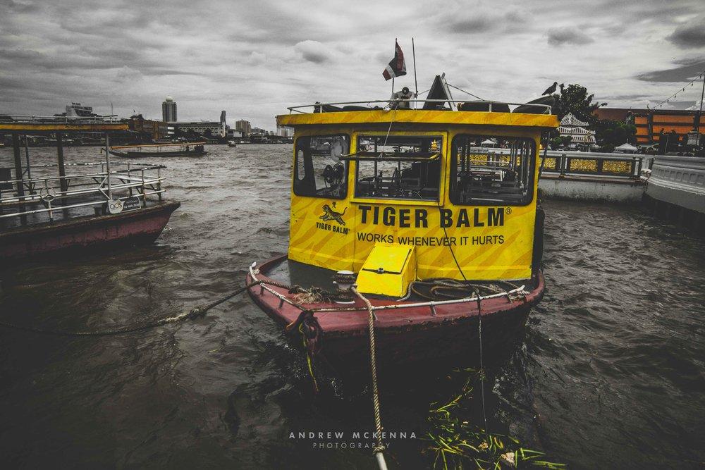 Wat Arun Temple Bangkok. Thailand, Photography by Andrew McKenna. tiger Balm Boat.