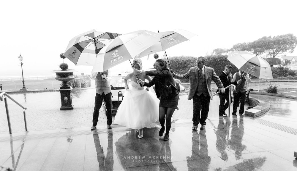 Staff at The Slieve Donard Resort & Spa keeping the rain of the bride & groom.