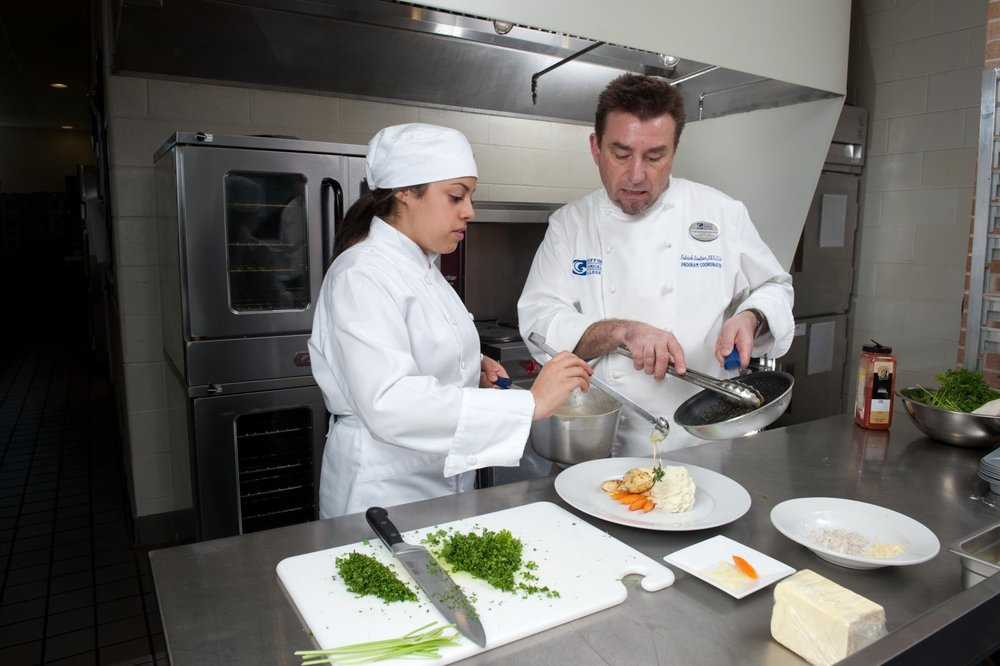 Image of a student in the kitchen with culinary instructor.