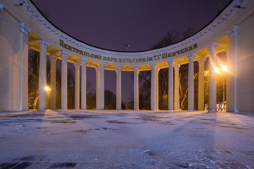 """""""Entrance"""" Beautiful gate to the T.G. Shevchenko Central Cultural Park in Dnipro. It was a particularly cold night, with some wind gusts that made for a memorable walk through the town. I set up my tripod low to the ground for this shot. Seeking out perfect symmetry for this shot, I aligned the camera with the center of the arch to create a powerful impression of this structure. It was very impressive in person, an appropriate entrance to a very beautiful park. I am happy with how this shot came out, and anyone who knows Dnipro can surely recognize this landmark easily! Canon 6D TS-E 17mm f/4L 30.0 sec at f / 8.0 17mm ISO 50 December 8, 2016"""