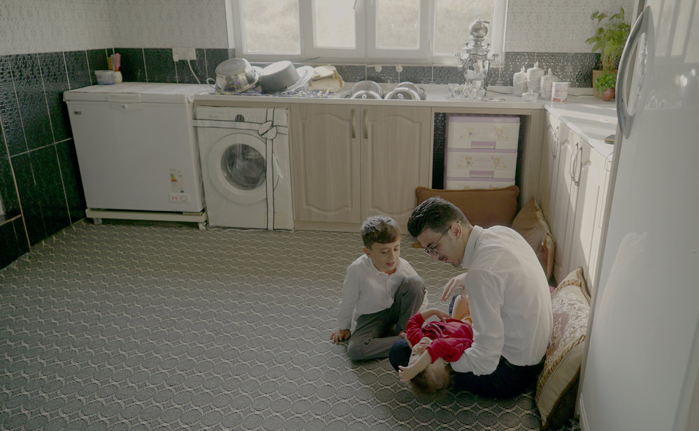 Kazo plays with his son and daughter in their kitchen in Soran, Iraq.