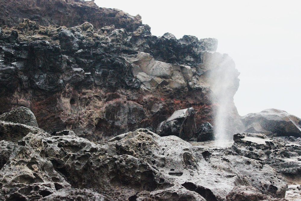 The natural wonder of the Nakelele Blowhole shooting sea water behind lava rock formations