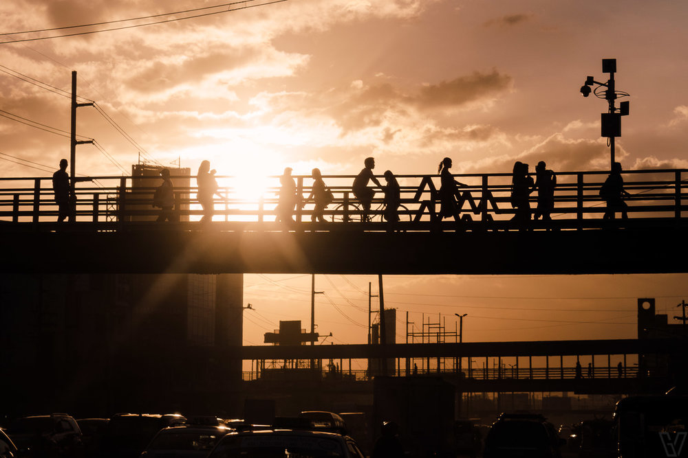 Sun setting behind people walking on the overpass.