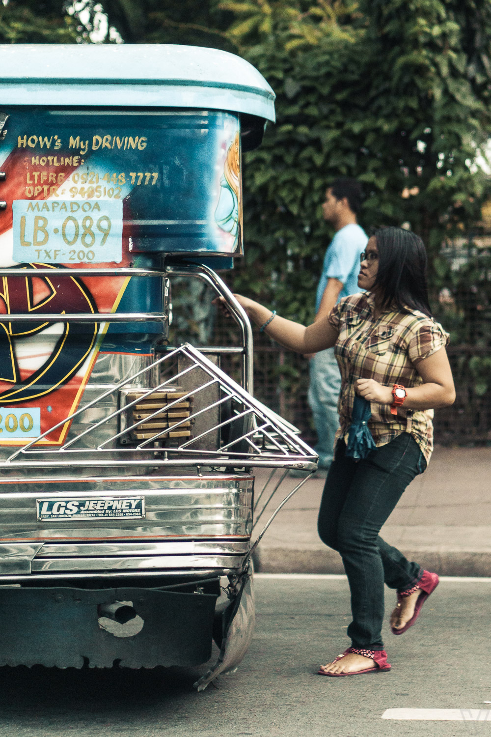 A woman getting on a jeepney.