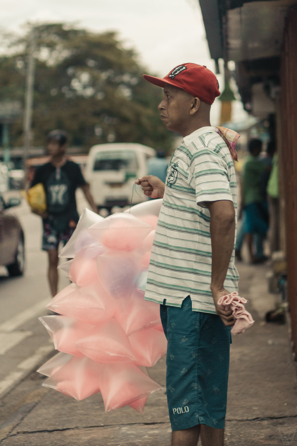 A guy holding bags of cotton candy.
