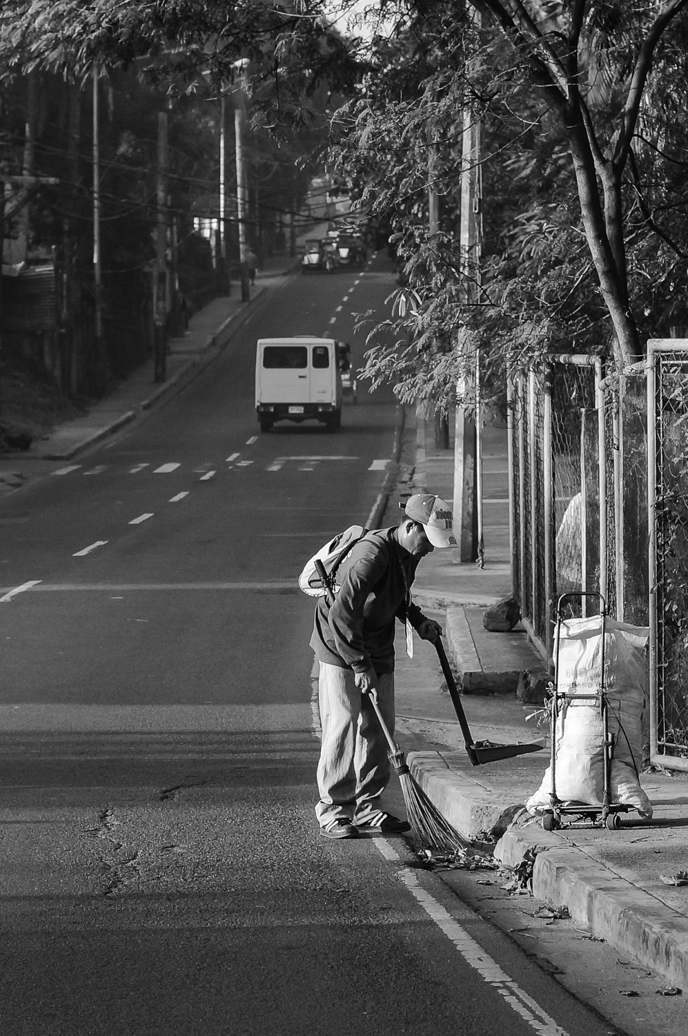 Sweeping the street early in the morning.