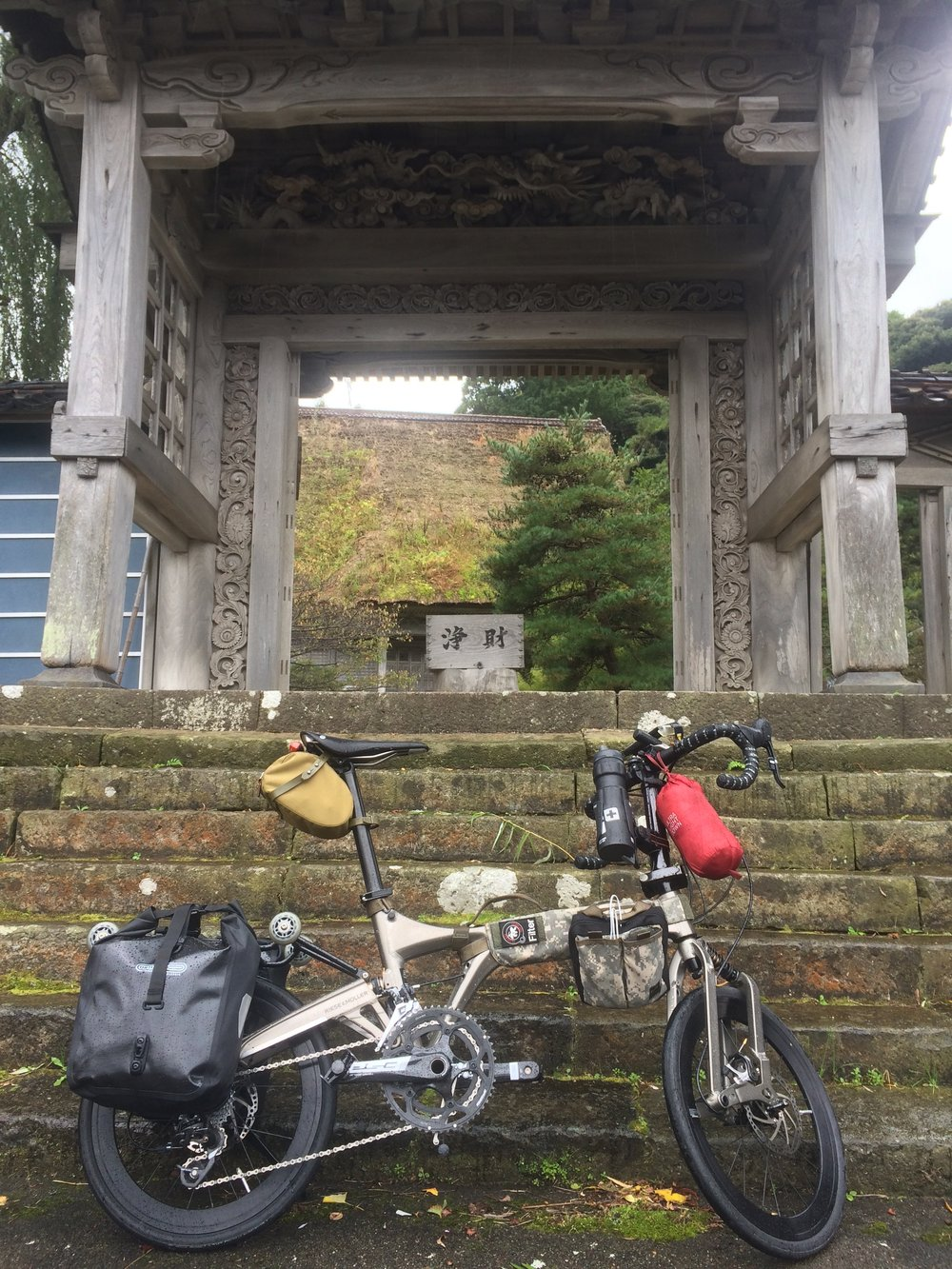 Parking in front of the old wooden temple gates.