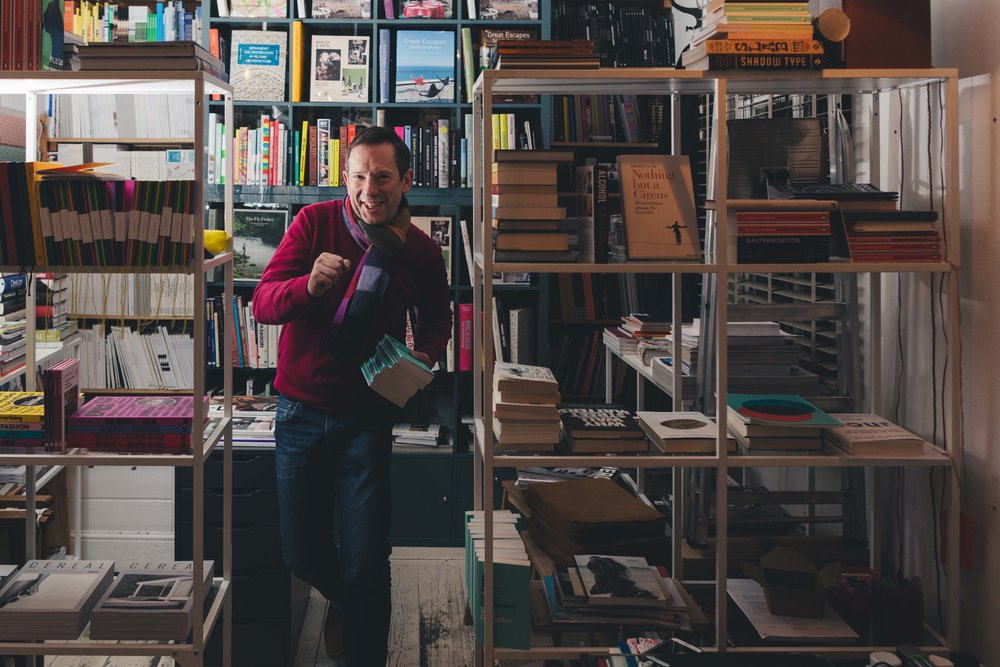 portrait of man moving towards camera in a playful way, surrounding by books