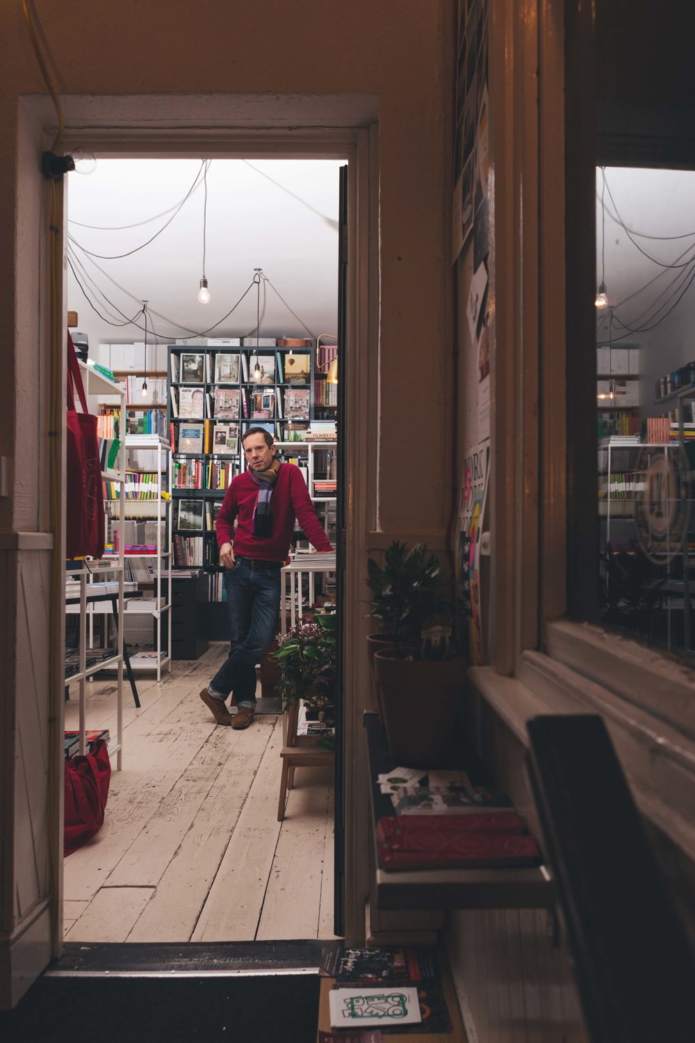 man in bookshop doorway, illuminated and lit up and surrounded by books