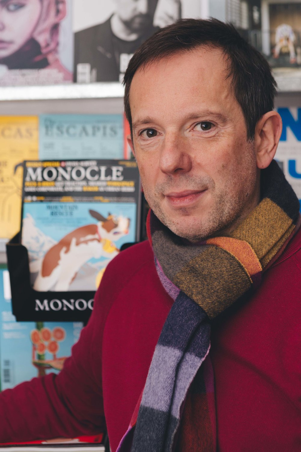 portrait of a man in a red jumper with a striped scarf looking to camera with books presented behind him