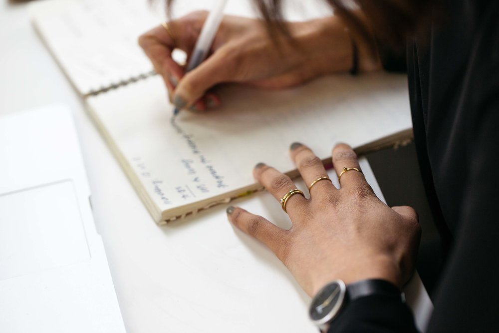 hands writing in a notebook on top of a white table. Captured by Natasha Boyes Photography.