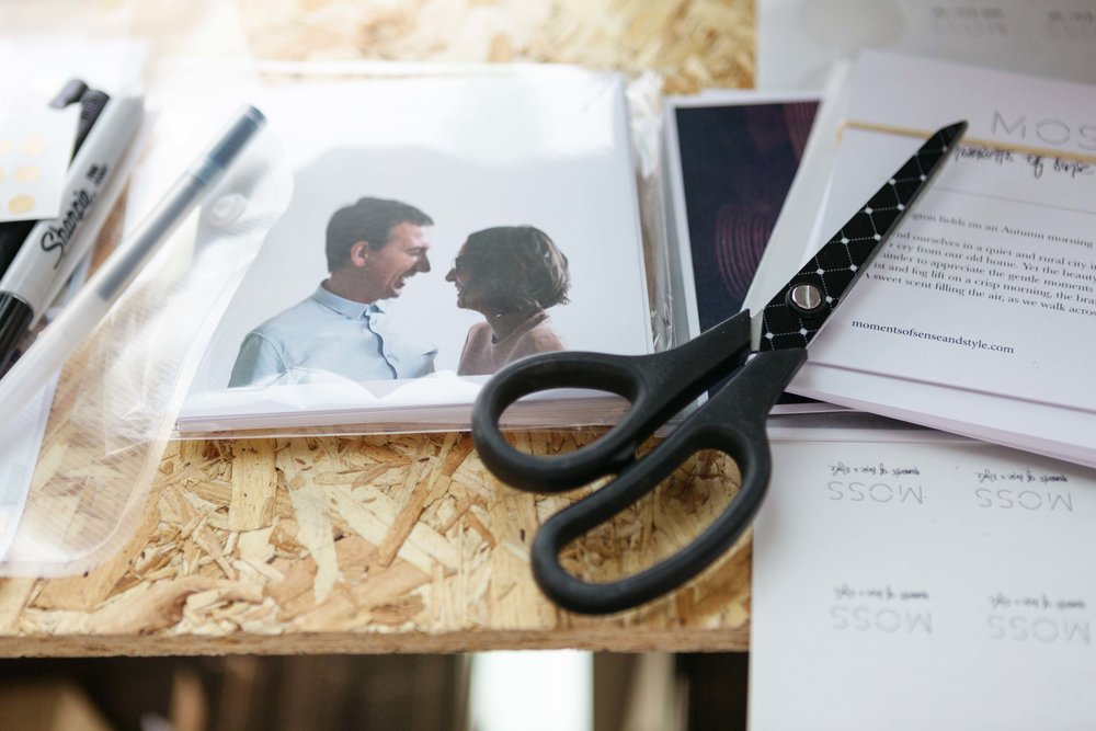 scissors, photograph and pens on top of wood, ready for packing up deliveries. Photo by Natasha Boyes Photography