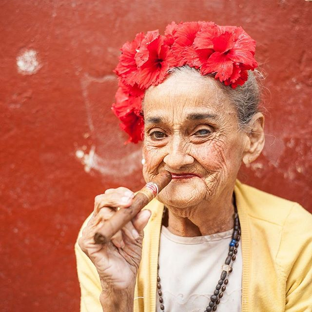 This is the cigar lady, and we see her enjoying a Cuban in the same place every time we're in Havana. And yes, the flowers are real 🌺✨