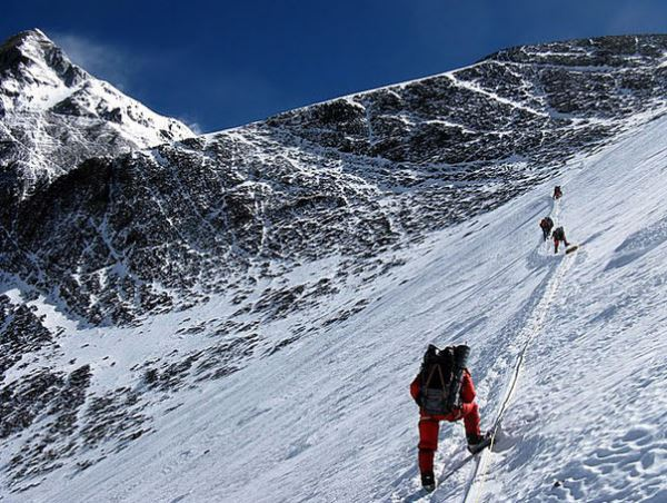 Climbers face high winds as they cross the snow field to the Geneva Spur, between them and the summit.   Photo from MountainGuides.com