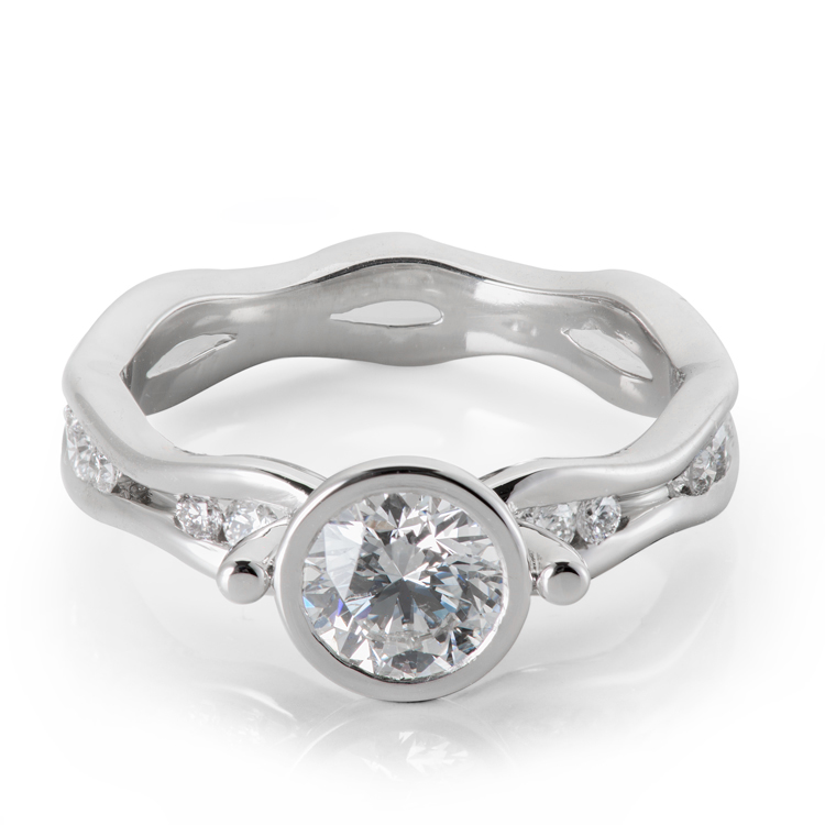 Custom made diamond engagement ring curving bands of gold holding small diamonds accenting a bezel set solitaire diamond