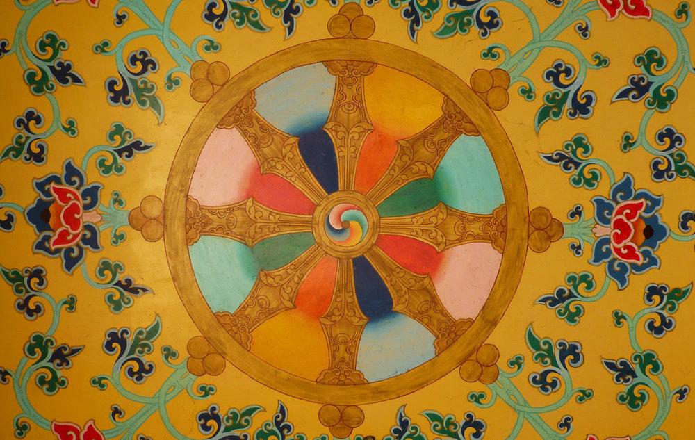"""Figura 9:  La """"rueda del Dharma"""", emblema del budismo, pintada en el techo del templo tibetano de Bodh-Gaya (Bihar), India. (Foto: Anandajoti/Wikimedia Commons)."""