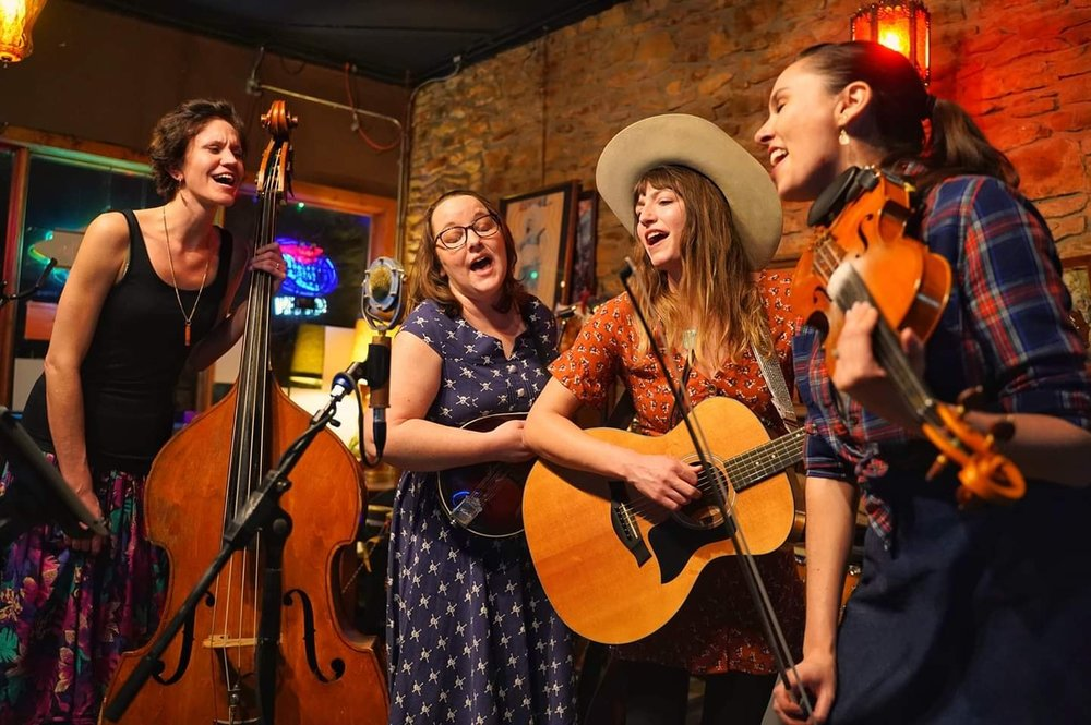 """Unfit Wives (picture above by Brian Byers) is a hard-driving, bluegrass band with Kahlen Mitchell on bass, Shannon Quick on fiddle, and Monica Greenwood on Mandolin. The video below is Unfit Wives singing """"Dreamin'"""" to a baby filmed by Fally Afani. Find Unfit Wives on Instagram and facebook and follow their upcoming shows!"""