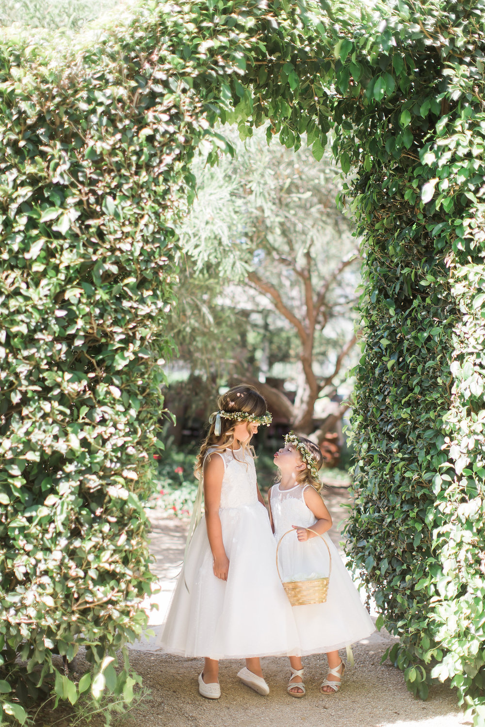 I placed these two adorable flower girls under this greenery and asked them to stand and look at me. Then I asked them to look at each other and she stuck her tongue out quickly. I, of course, kept snapping as I laughed. Some photographers might not use this image, however, I love how natural it feels. The photo is fun and playful, a total representation of my brand. Sometimes part of the art form is choosing which moments you feel are important to show to your audience.
