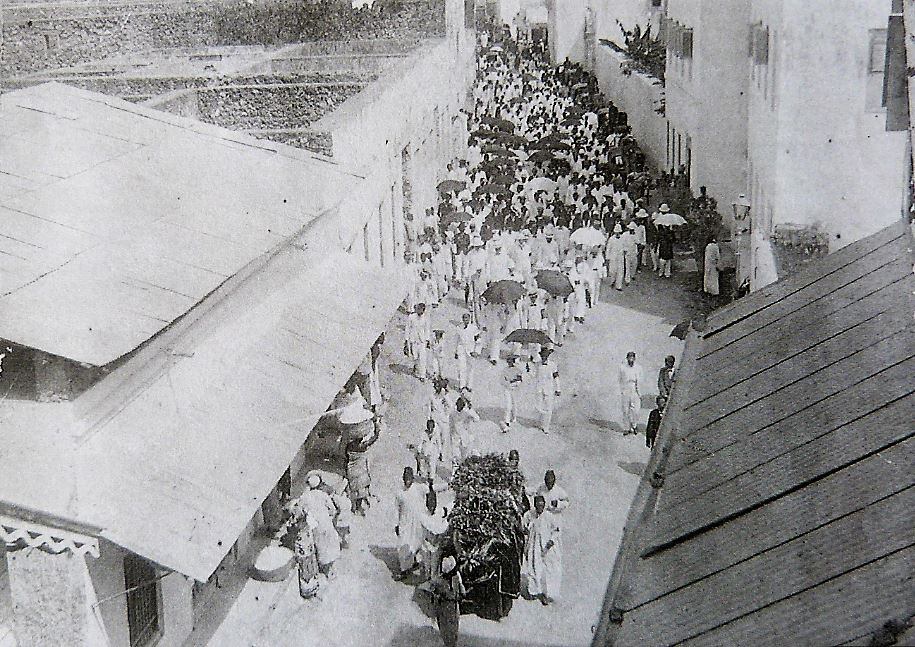 Augusto Bras de Sousa's funeral procession being led down the streets of Zanzibar, 1902. It was customary for the entire population of Goans in Zanzibar to attend the funeral and Goan shops along the route of the procession would close as a mark of respect. The Catholic cemetery in Zanzibar was funded and built by Goans. Photo cannot be reproduced without permission of Ze Muller.