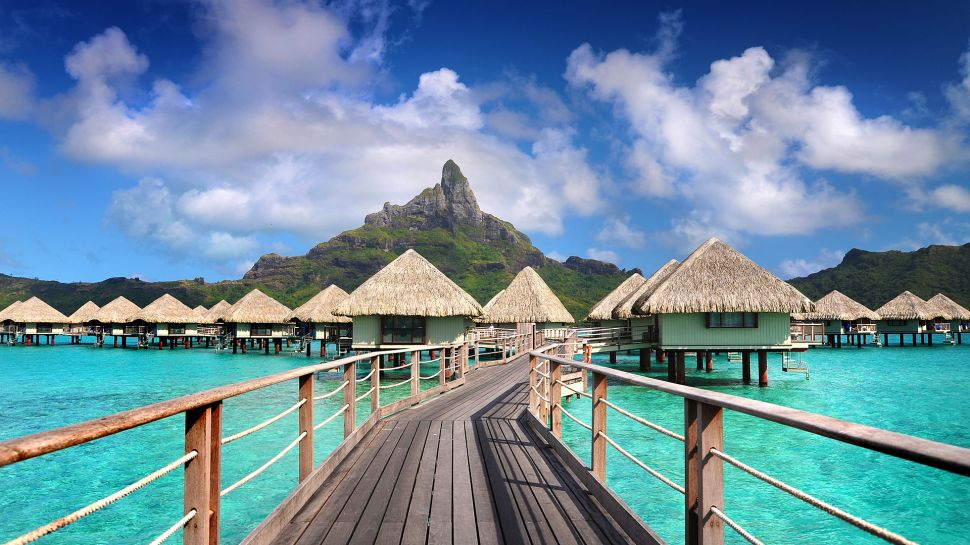 The small island of Bora Bora (just 6 miles long and more than 2 miles wide) overflows with beauty. Dormant volcanoes rise up at its center and fan out into lush jungle before spilling into an aquamarine lagoon. The very definition of a tropical getaway, blissful Bora Bora abounds with luxurious resorts, sunny skies, warm waters and friendly locals