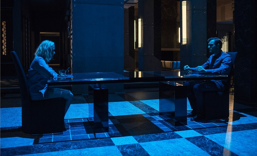 Julia and Alex sit down for dinner in the cold, literally blue, clinical looking dining room in an extremely Modernist mansion.
