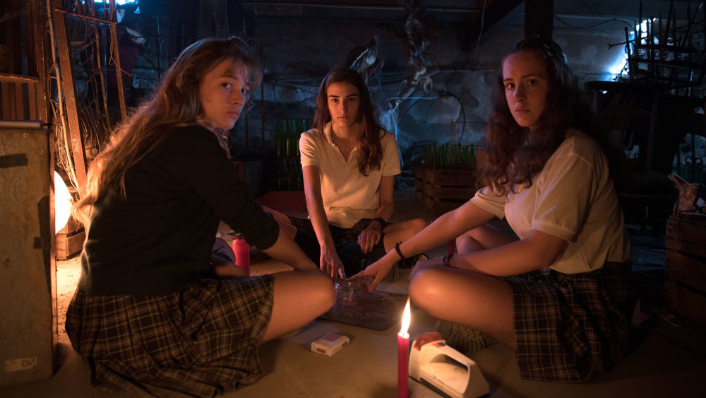 Veronica and her friends play with a Ouija board in the Catholic school basement, which even by 1991 they should have known was a terrible idea.