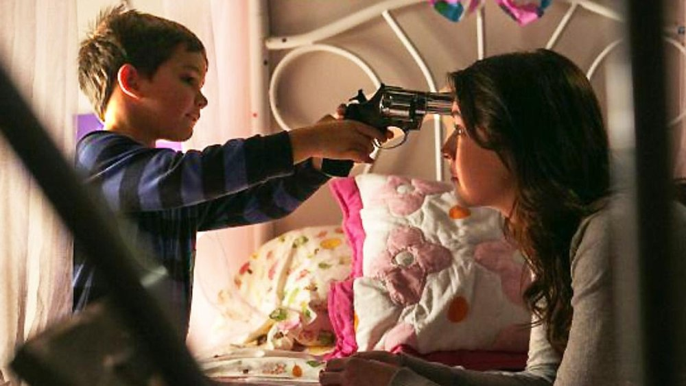 I think the picture speaks for itself. The youngest actor is asked to pull the trigger on what he's told is a dangerous gun by the babysitter character. Why?