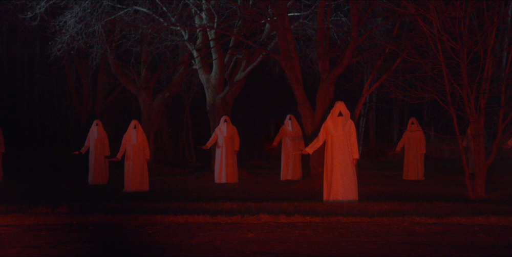 """""""Alien"""" is a loose term here. It doesn't have to be extraterrestrials. It's an outside invasive species with ambiguous origins. Maybe this triangle-faced cult standing menacingly in the woods outside has some idea of where they came from."""